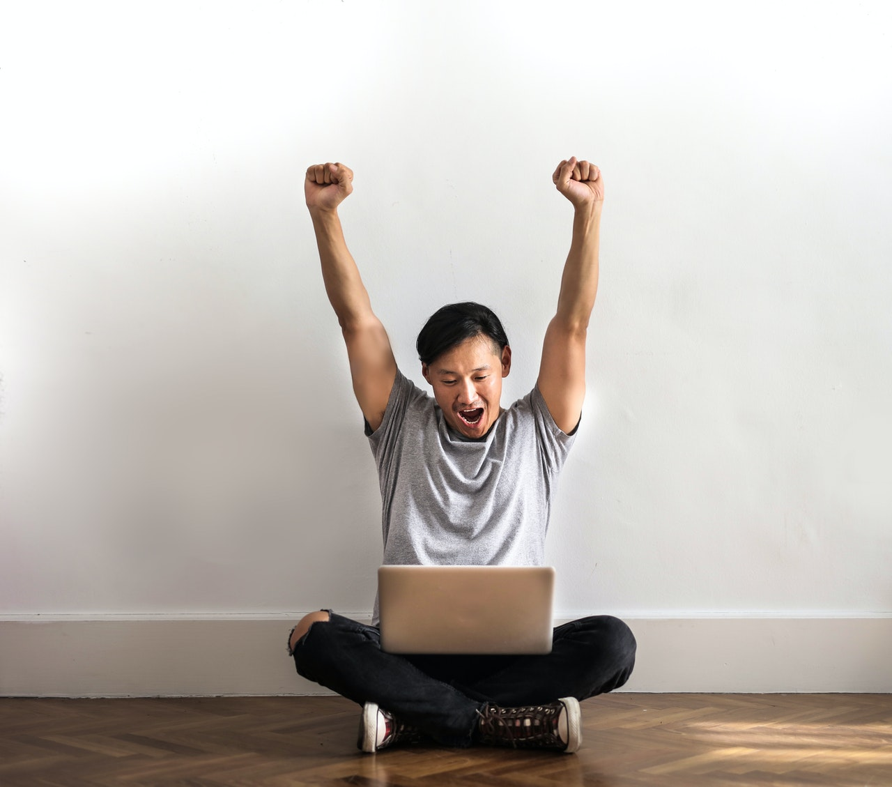 man cheering stretching arms up