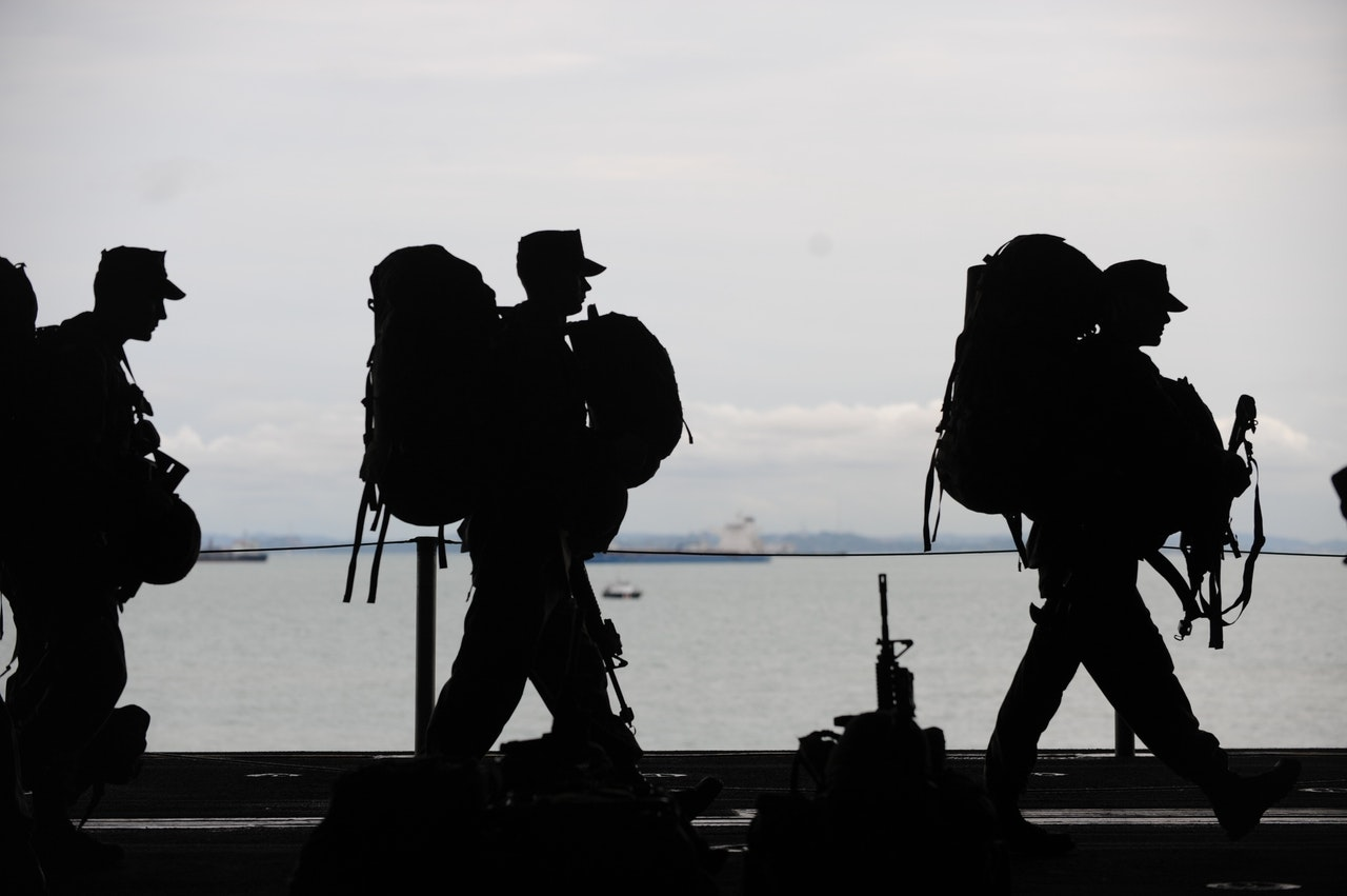 silhouette of soldiers carrying equipment