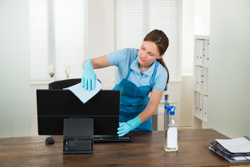 woman sanitizing workspace